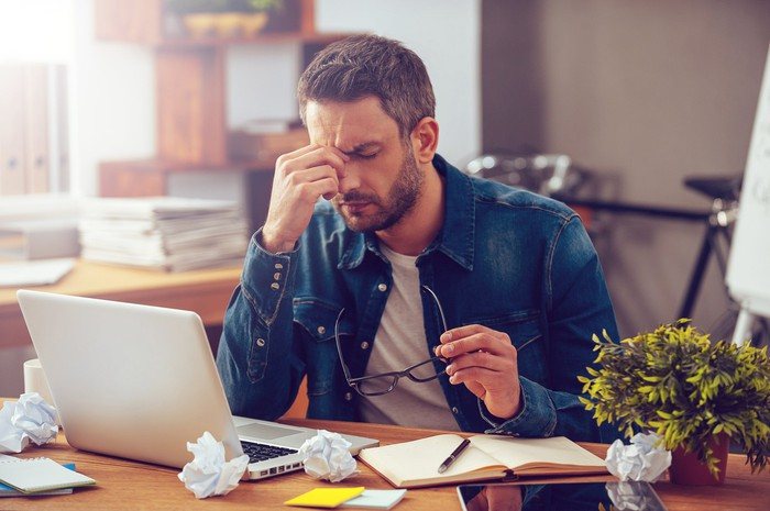 Frustrated man looking at laptop.