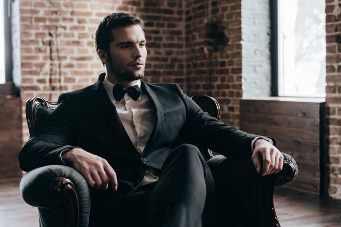 Man in tuxedo sitting in chair