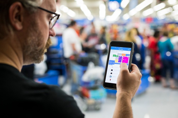 A man holds his phone with the Wal-Mart app open in a Wal-Mart