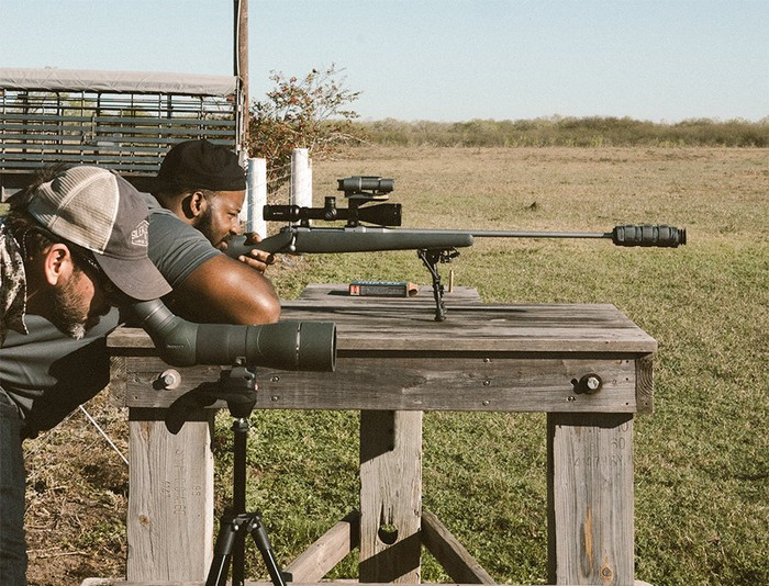 Pro footballer Fletcher Cox siting in a rifle outfitted with a supressor