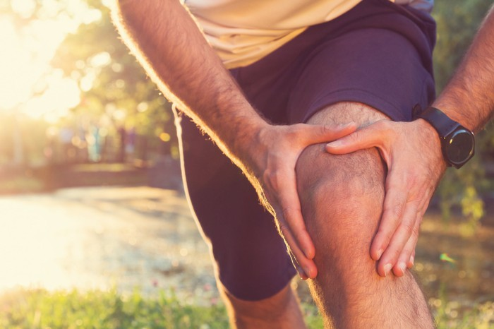 A runner rubs his knee in pain.