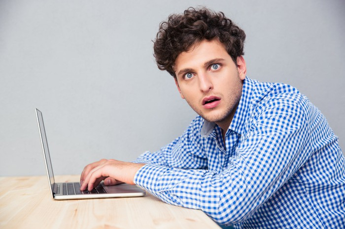 A man seated before a laptop gives a surprised expression.
