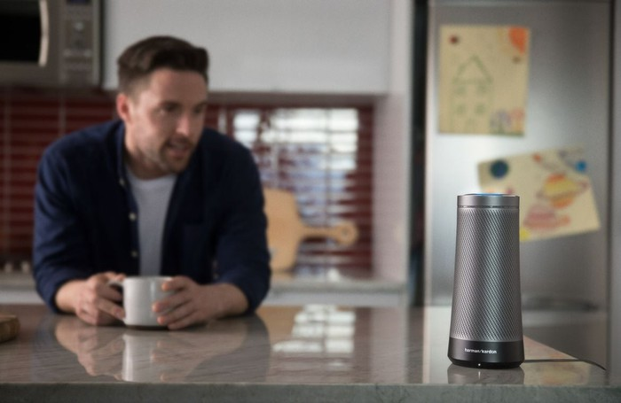 Cylindrical smart speaker on kitchen counter, while man with cup of coffee speaks to it.