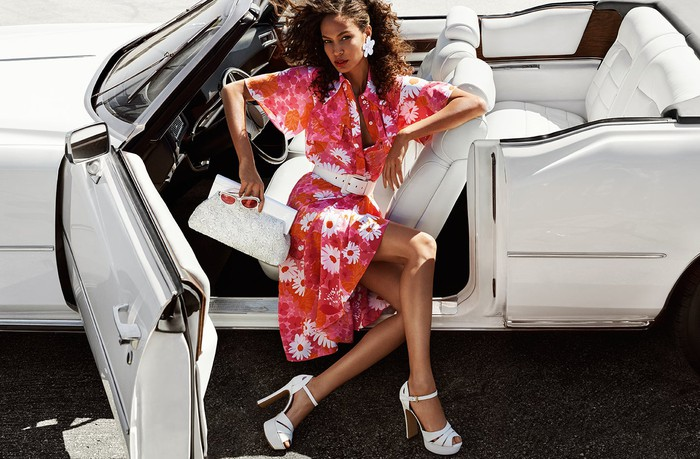 A Michael Kors product ad, featuring a woman in a red flowered dress, clutching a handbag, as she sits in a white convertible.