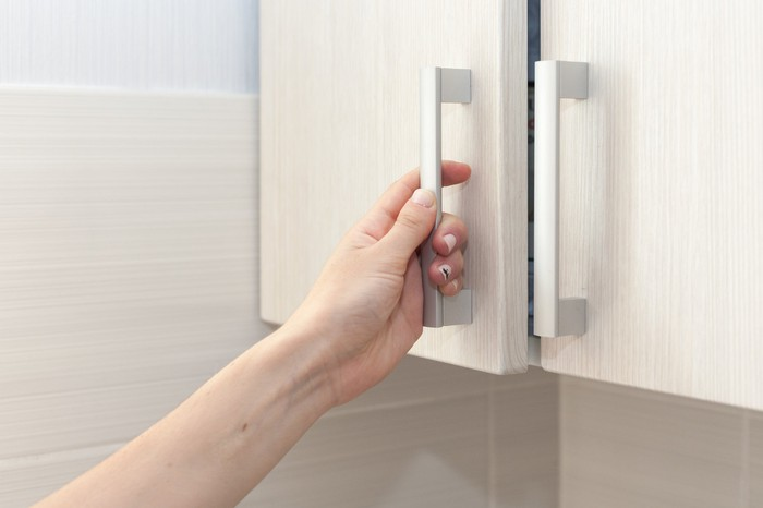 A hand pulls a cupboard door open.
