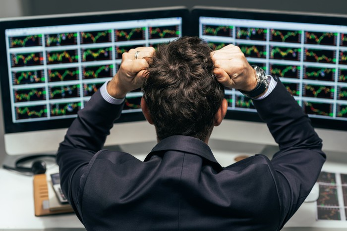 A stressed trader stares at numerous financial charts on two computer screens.