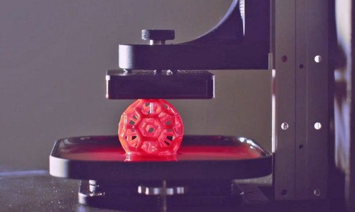A spherical polymer object built in a soccer ball pattern of hexagons and pentagons, rising from a pool of resin in a Carbon 3D printer.