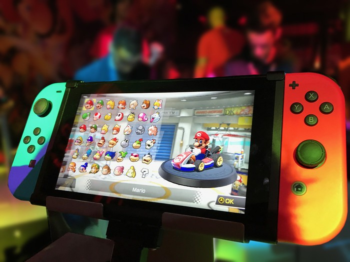 Nintendo Switch with red and neon blue controllers attached to the side of the devices screen, powered on with a Mario game on the screen.
