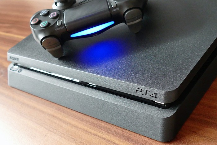 Sony Playstation 4 console laying on top of wooden table with controller laying on top of the console and powered on.