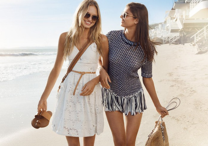 Two models walking down the beach in Michael Kors apparel