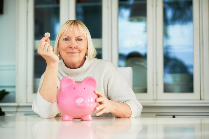 A woman holding up a coin by a piggy bank.