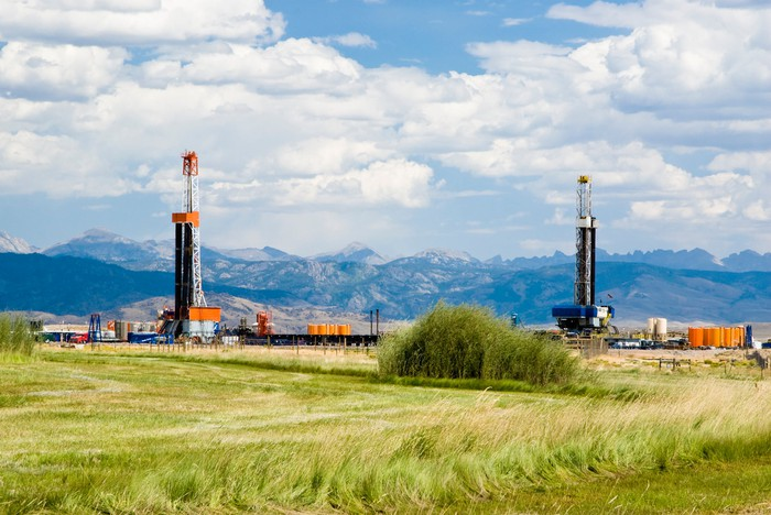Drilling rigs working in a field with a mountain range in the background.