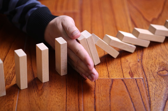 A hand stops a row of dominoes from falling.