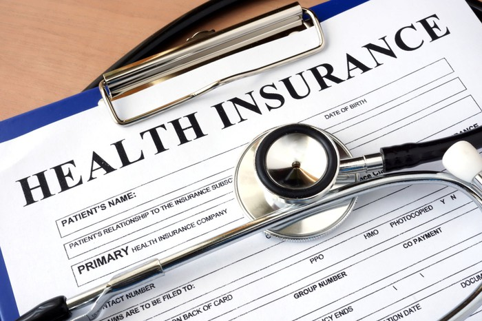 A health insurance enrollment form with a stethoscope lying on top.