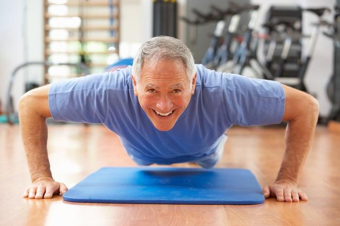Senior Man Doing Press Ups In Gym Smiling To Camera