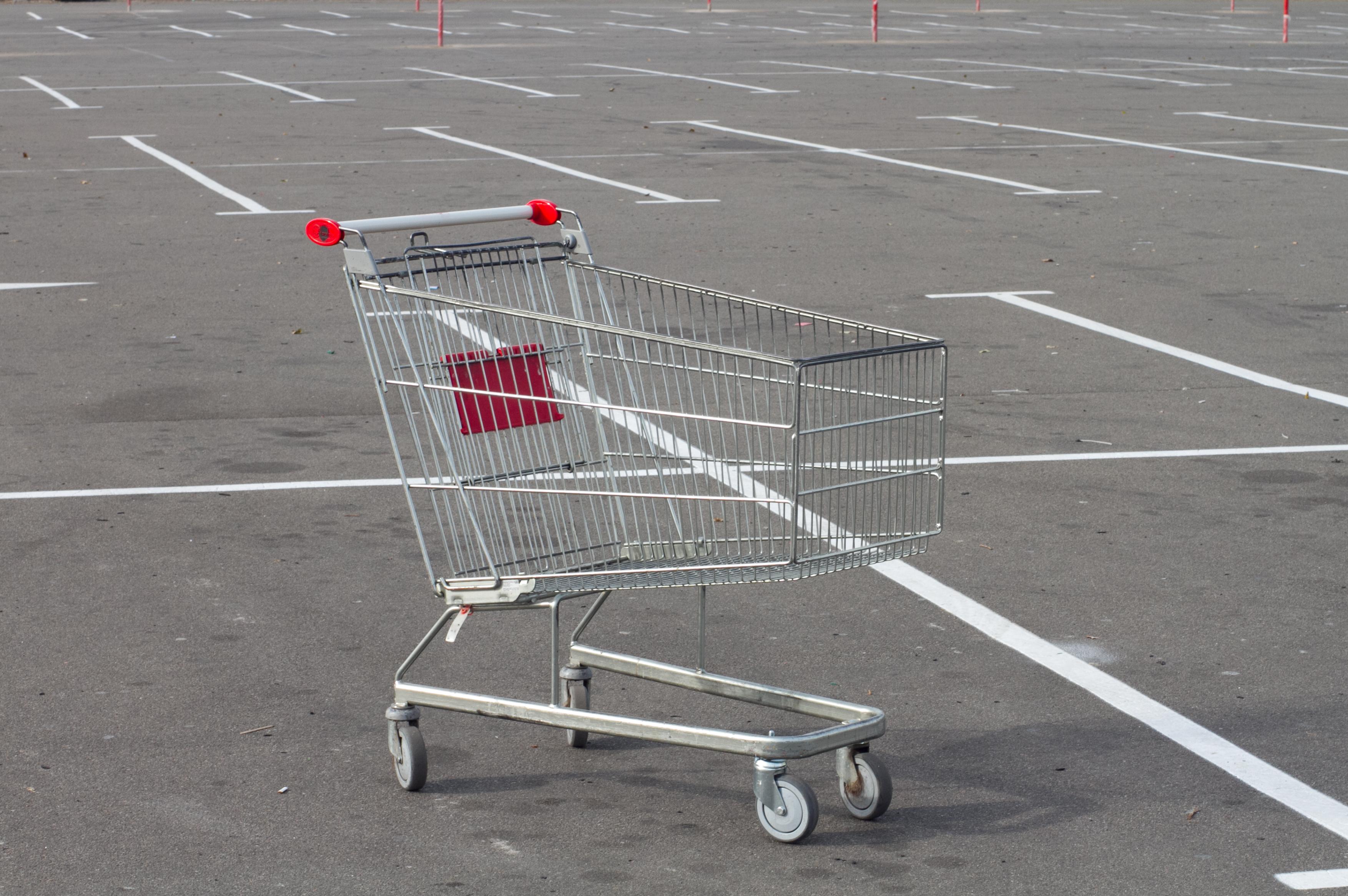An empty shopping cart sitting in an empty parking lot.