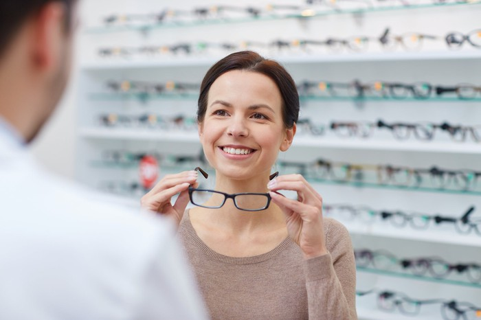 A woman tries on eyeglasses.