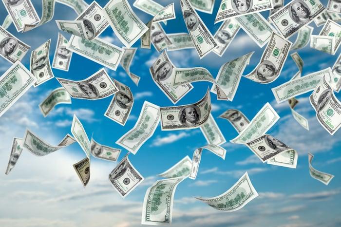 Hundred dollar bills falling from sky.