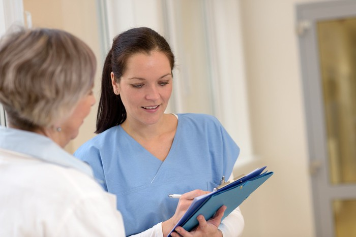 Nurse speaks to an older patient and fills out her chart.