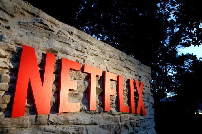 Bright red Netflix logo on a dark rock wall outside the company's headquarters in Los Gatos, CA.