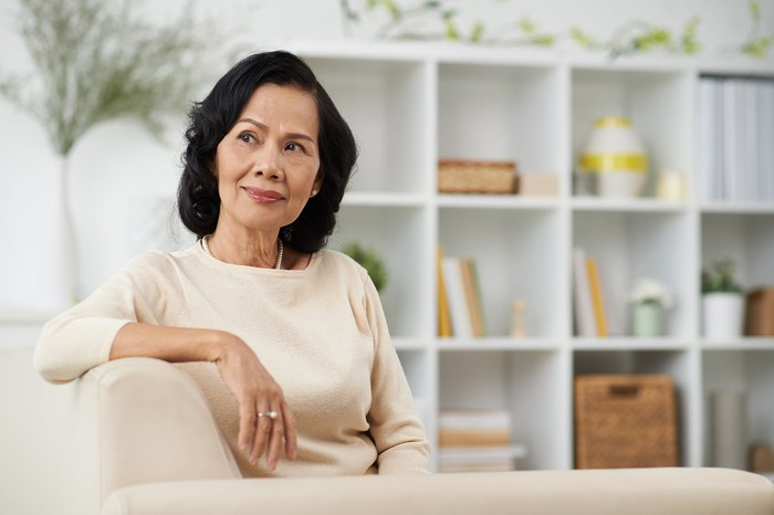 Senior woman sitting on couch and thinking