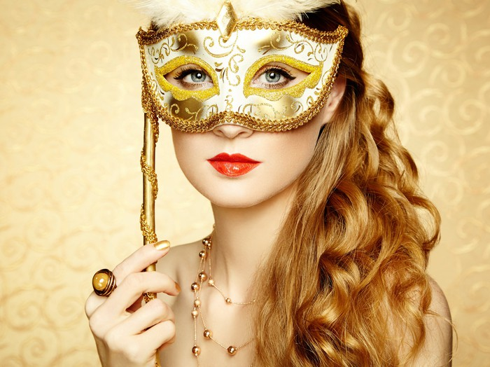A woman holds a gold masquerade mask in front of her face.