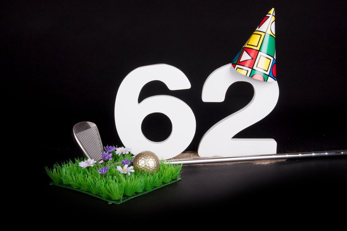 A golf club and golf ball on an artificial piece of grass, with the number 62