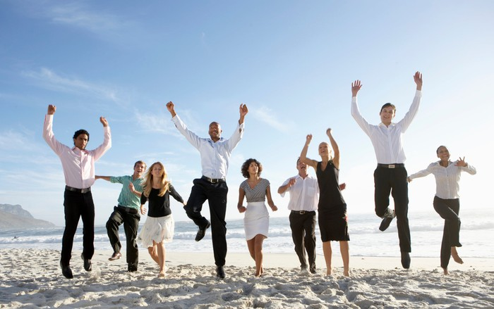 Business people jump for joy on a beach on a bright, sunny day.
