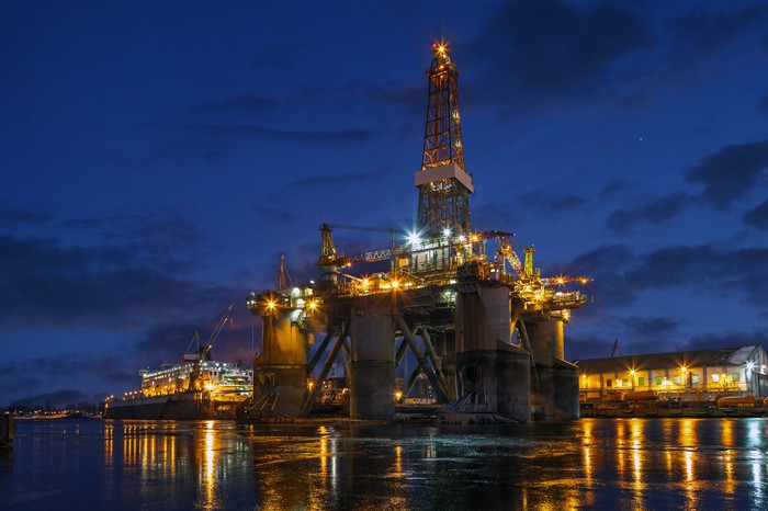 An offshore rig in dock at night