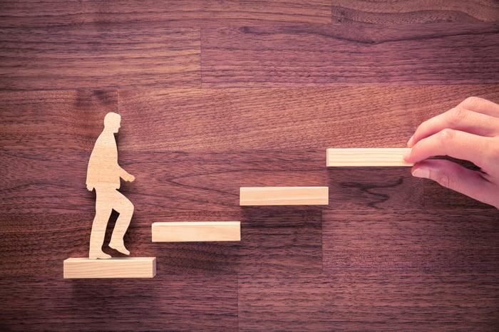 A wooden man walks up wooden steps.