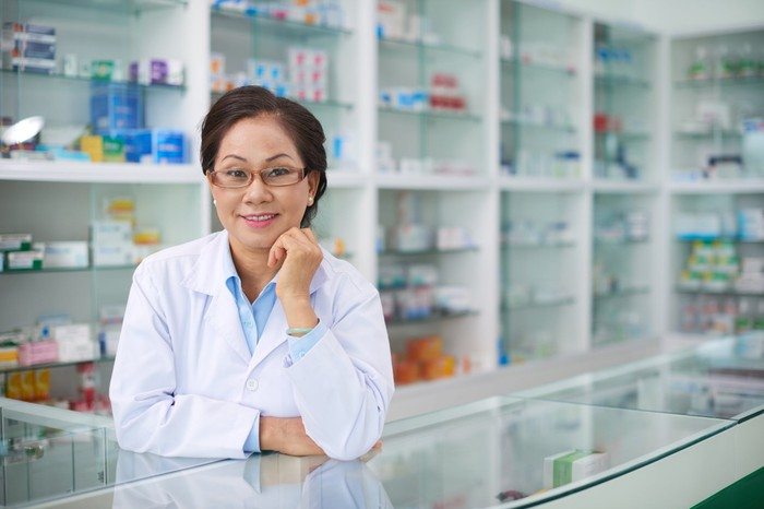 A pharmacist poses at a pharmacy counter.