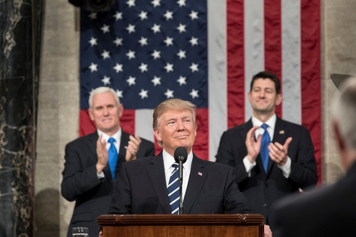 President Donald Trump standing at podium with Vice President Mike Pence and House Speaker Paul Ryan in the background