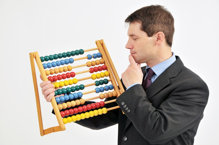 A businessman using an abacus.