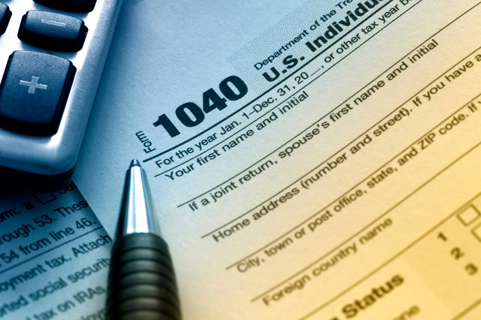 An IRS 1040 tax form next to a calculator and pen.