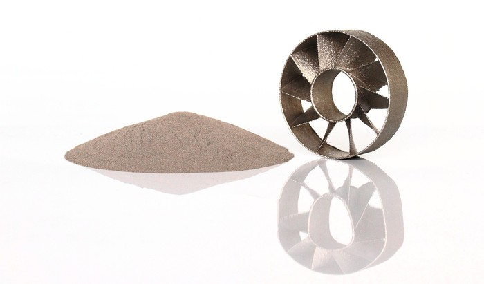 A 3D-printed metal part next to metal powder.