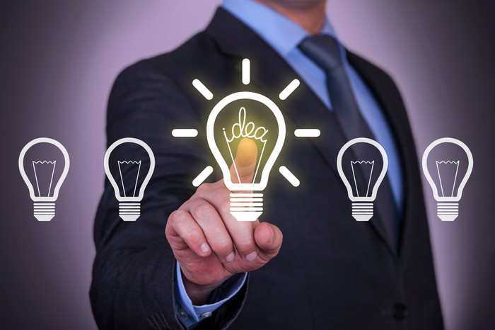A business person points at a lit up light bulb among a row of unlit light bulbs.