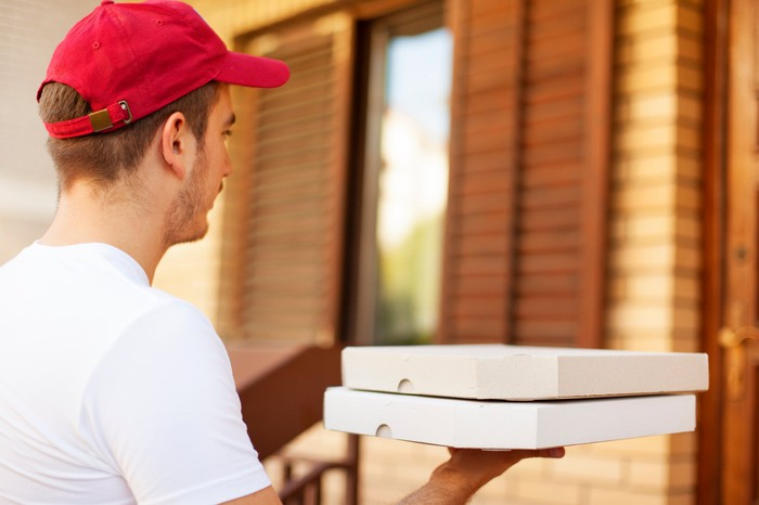 A delivery man bringing two pizzas to a house.