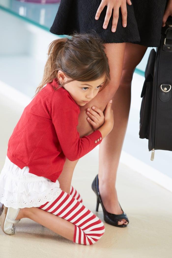 Girl holding onto her mom's leg