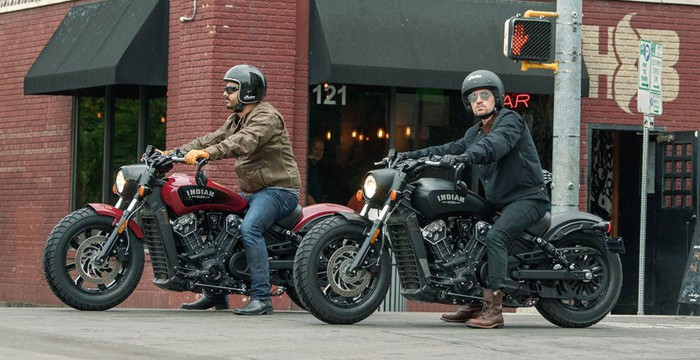 Two new Indian Scout Bobbers, one red, one black, with a male rider astride each, stopped outside a brick-building corner bar
