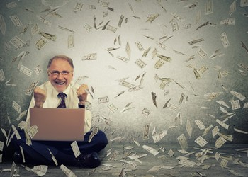 Senior man with laptop and money falling from above --GettyImages-503765192