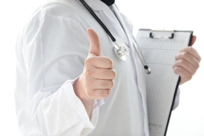 A doctor holding a clipboard and giving the thumbs-up sign.