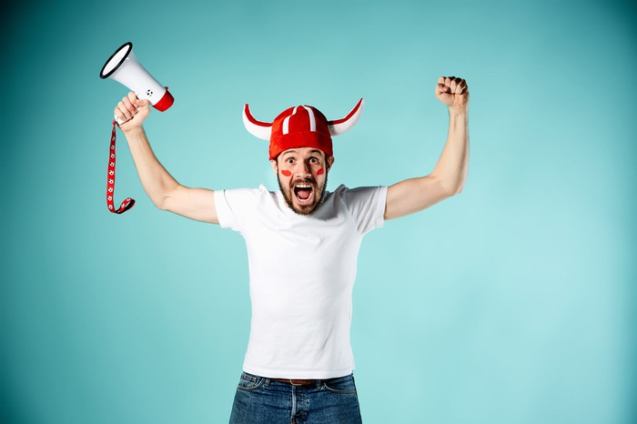 A sports fan raises his arms in celebration, holding a bullhorn in one hand.