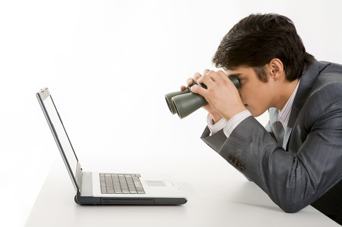 Man using binoculars to give a laptop computer a closer look.