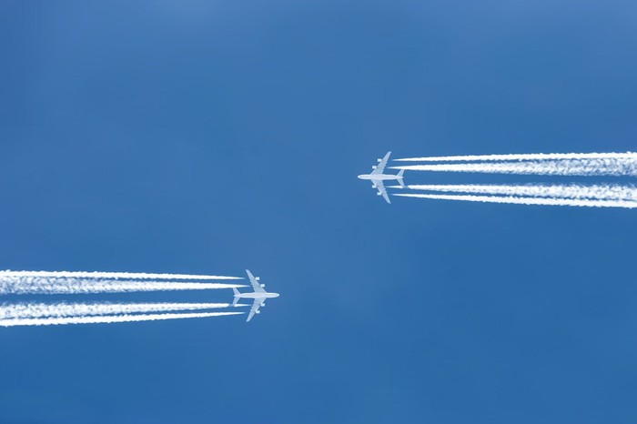 Two airplanes flying toward one another