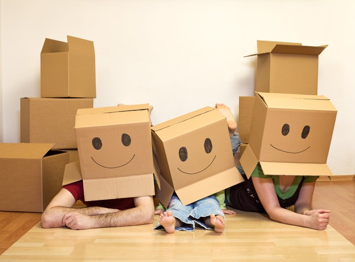 A family playing with cardboard boxes.