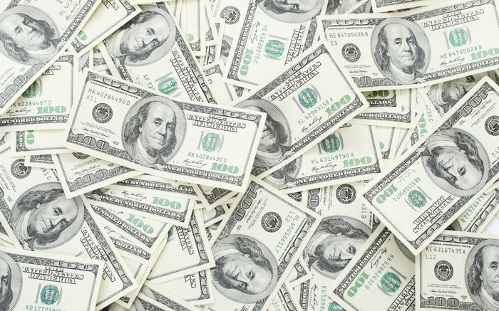 Hundred-dollar bills are scattered into a pile.