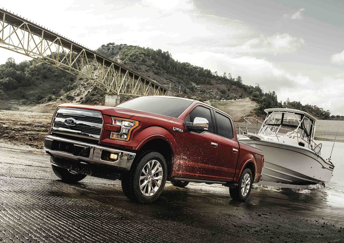 A red 2017 Ford F-150 pickup towing a boat