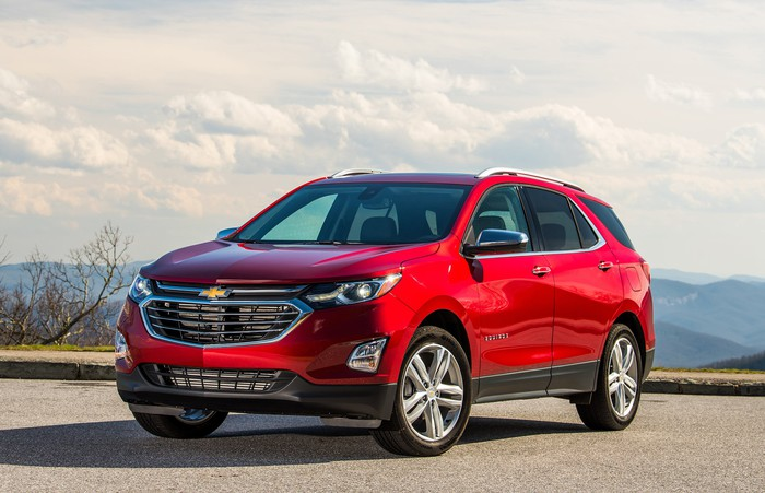 A red 2018 Chevrolet Equinox crossover SUV in a parking lot with mountains and sky visible in the background.