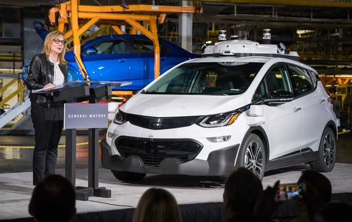 GM CEO Mary Barra at a podium next to a Chevrolet Bolt EV with self-driving sensors, at GM's Orion Assembly Plant in Michigan.