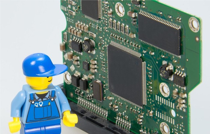 A Lego figure standing next to a circuit board.